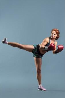 Rijpe atletische roodharige vrouw in sportkleding