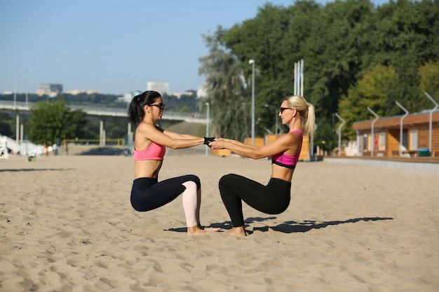 Rijpe atletische vrouwen die sportkleding en zonnebril dragen die samen op het strand hurken