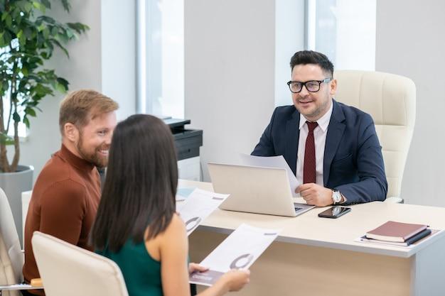 Rijpe auditor in formalwear die een jong stel in zijn kantoor raadpleegt