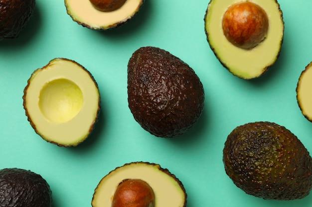 Rijpe avocado op munt achtergrond, bovenaanzicht