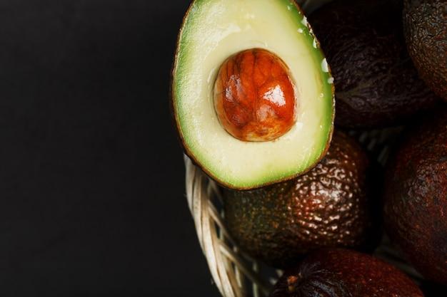 Rijpe avocado's in een mand op een zwarte tafel, met een gesneden fruit en een pit