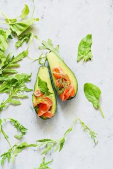 Rijpe avocadoboten met plakjes gezouten forel, zalm en verse groenten. avocadoboten met zalm met kalk, spinaziebladeren en rucola worden gevuld, concepten gezond voedsel, dieet.