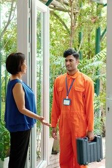 Rijpe aziatische eigenaar handgebaar terwijl hij richting de kamer wijst en jonge indiase loodgieter begroet met werktas
