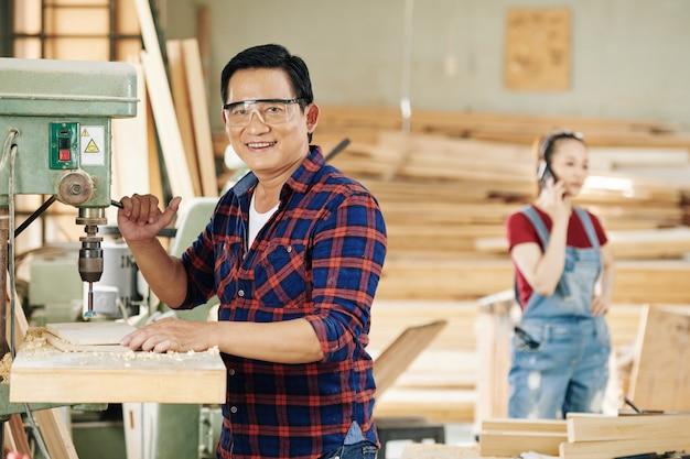 Rijpe aziatische timmerman in beschermende bril die gaten in houten plank boort met behulp van speciale machine