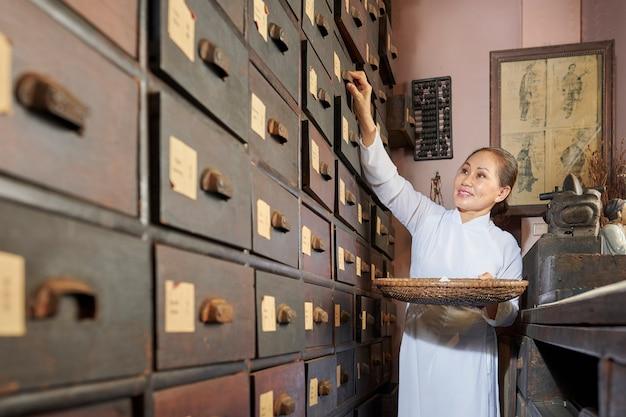 Rijpe aziatische vrouw die lade in apotheker opent