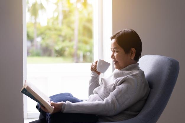 Rijpe aziatische vrouw die 's ochtends thuis koffie drinkt, gelukkig en glimlachend, positief denken, gezondheidszorg senior verzekeringsconcept
