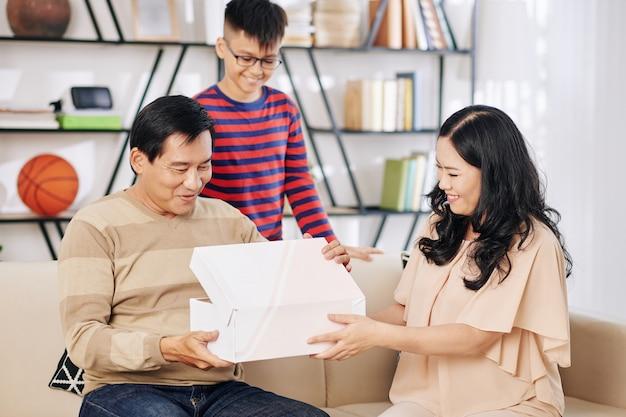 Rijpe aziatische vrouw die verjaardagscadeau van haar en hun zoon geeft aan opgewekte echtgenoot