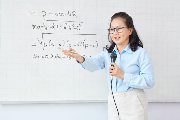 Rijpe aziatische vrouwelijke wiskundeleraar die in microfoon spreekt wanneer student vraagt om vergelijking op whiteboard op te lossen