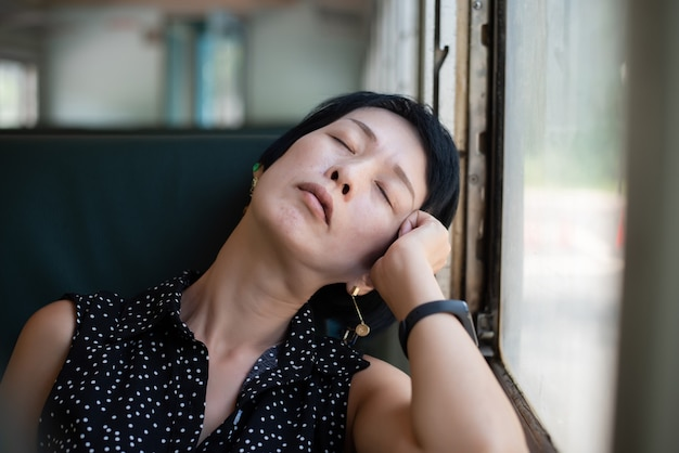 Rijpe aziatische vrouwenslaap in het treinwagon