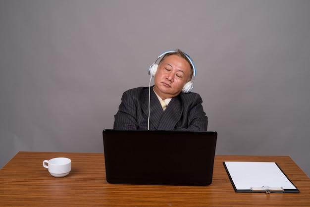 Rijpe aziatische zakenmanzitting met houten lijst tegen grijs