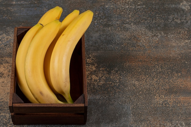Rijpe bananen in de doos, op het marmeren oppervlak