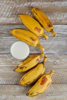 Rijpe bananen met melk bovenaanzicht op een houten