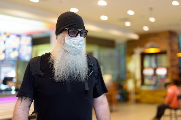 Rijpe bebaarde hipster man als backpacker met masker en zonnebril denken in het winkelcentrum