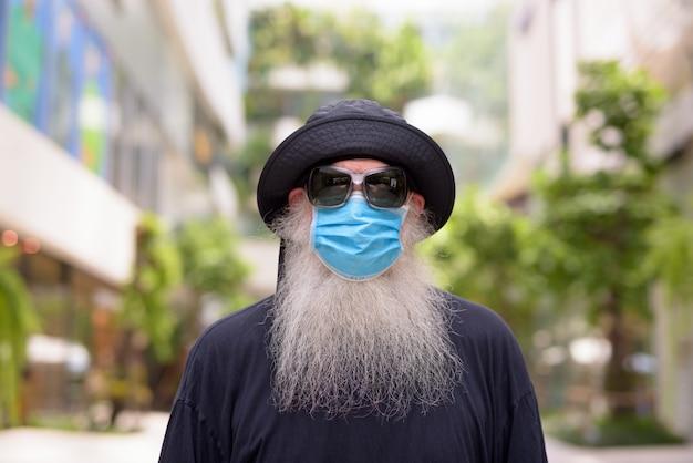 Rijpe bebaarde hipster man met hoed en masker ter bescherming tegen het coronavirus in de stad