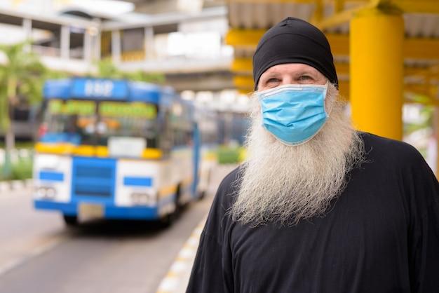 Rijpe bebaarde hipster man met masker voor bescherming tegen het uitbreken van het coronavirus en vervuiling bij de bushalte