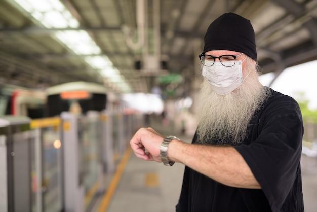Rijpe bebaarde hipster man met masker voor bescherming tegen uitbraak van het coronavirus en controleert de tijd op het treinstation