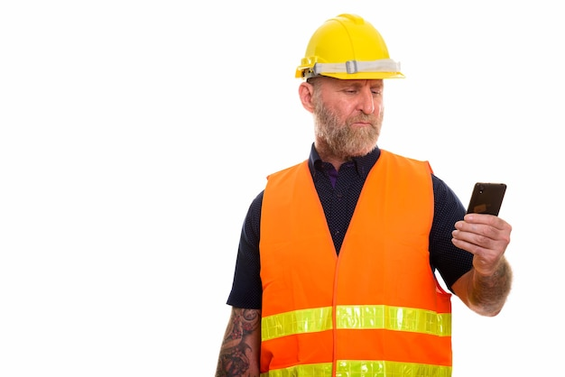 Rijpe bebaarde man bouwvakker met behulp van mobiele telefoon
