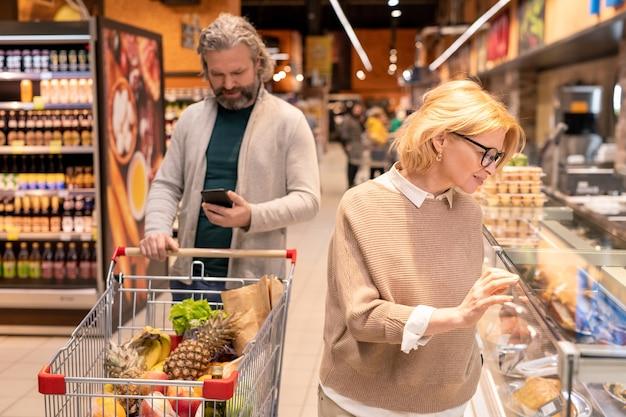 Rijpe bebaarde man die door boodschappenlijst in smartphone kijkt en kar duwt terwijl zijn vrouw zich door zeevruchten bevindt