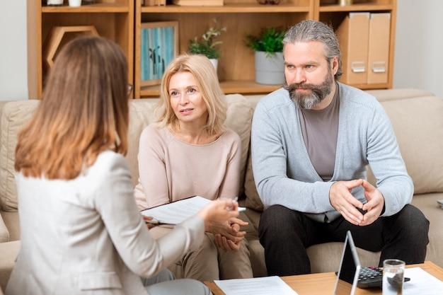 Rijpe bebaarde man en zijn vrouw zittend op de bank en overleg met de makelaar over het kopen van een nieuw huis