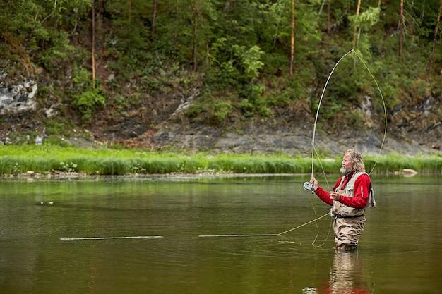 Rijpe bebaarde man in waterdichte kleding tijdens het vliegvissen in de rivier in het bos.