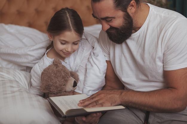 Rijpe bebaarde man rust thuis met zijn kleine dochter
