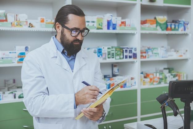 Rijpe bebaarde phrmacist die werkt bij is drogisterij