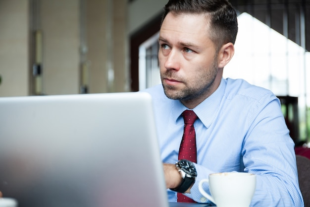 Rijpe bedrijfsmens die een kopje koffie in een coffeeshop heeft en aan zijn laptop werkt