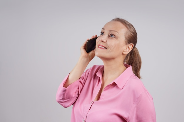 Rijpe bedrijfsvrouw die in roze blouse op celtelefoon spreekt. foto op een grijze achtergrond met kopie ruimte.