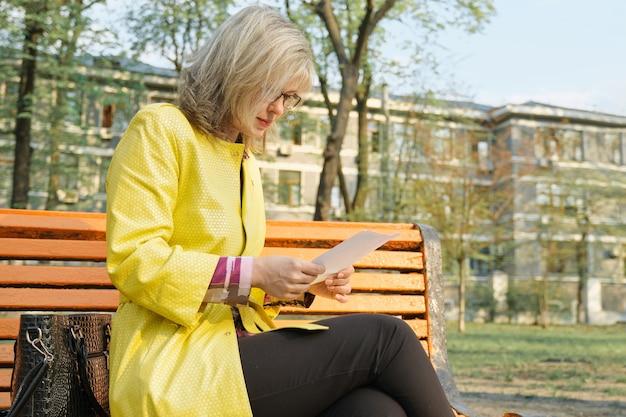 Rijpe bedrijfsvrouw die met glazen document leest