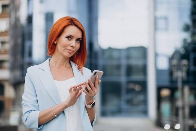 Rijpe bedrijfsvrouw die op de telefoon spreekt