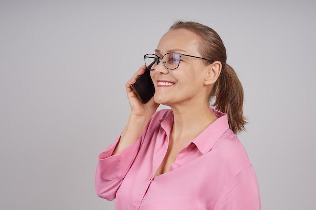 Rijpe bedrijfsvrouw in glazen, in een roze blouse die op een celtelefoon spreekt. foto op een grijze achtergrond met kopie ruimte.