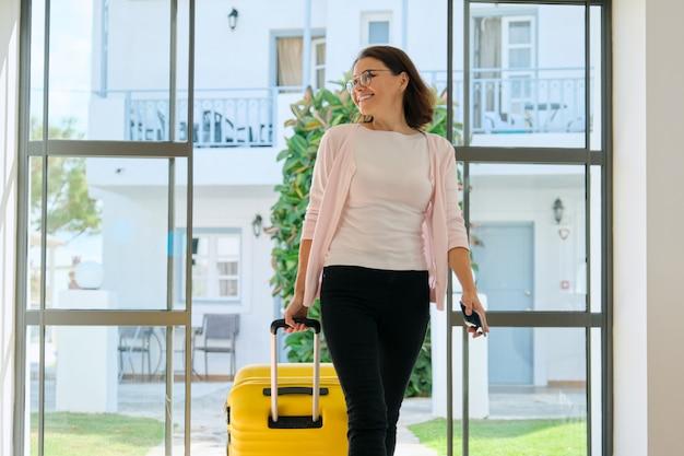 Rijpe bedrijfsvrouw in hotelbinnenland met koffer