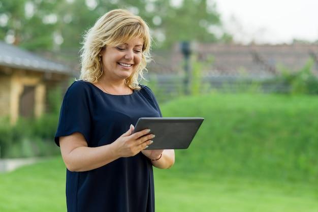 Rijpe bedrijfsvrouw met digitale tablet