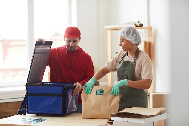 Rijpe bezorger die bestellingen inpakt om de doos te koelen bij de bezorgservice voor eten