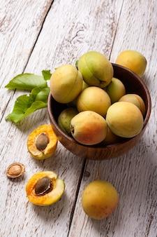 Rijpe biologische abrikozenvruchten in de houten kom van de asboom op een witte houten lijst