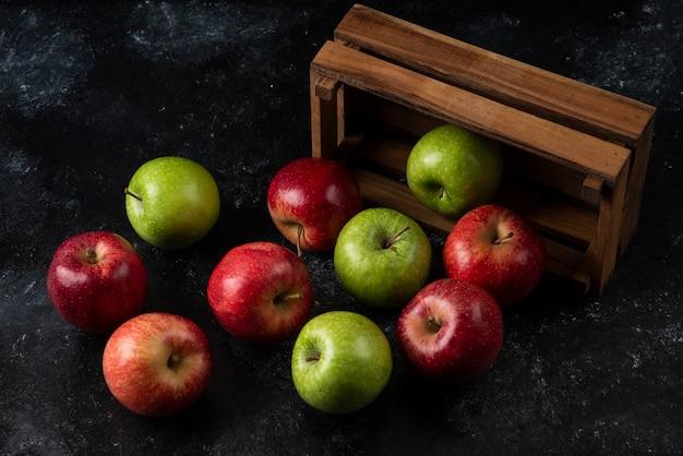 Rijpe biologische appels uit houten kist op zwarte ondergrond. .
