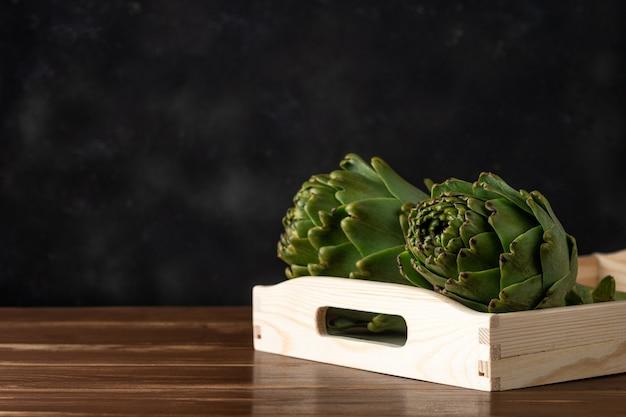 Rijpe biologische artisjokken op een rustieke houten tafel.