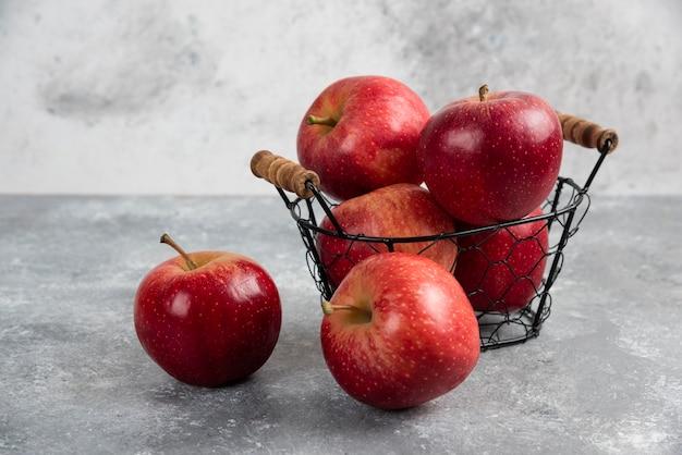 Rijpe biologische rode appels in metalen mand op zwart.