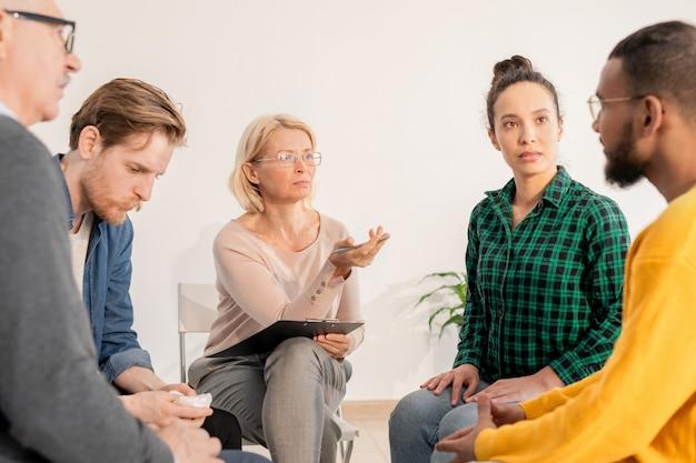 Rijpe blonde counselor wijst naar een van de patiënten terwijl hij zijn probleem met de groep bespreekt