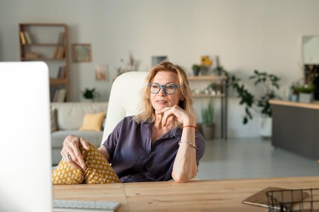 Rijpe blonde ontspannen zakenvrouw computerscherm kijken terwijl zittend door tafel voor monitor en kijken naar online film thuis