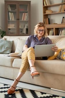 Rijpe blonde ontspannen zakenvrouw kijken naar tablet-display zittend op de bank en kijken naar online film in de thuisomgeving