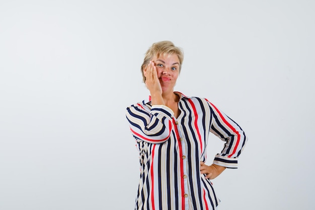 Rijpe blonde vrouw in een overhemd met verticale strepen