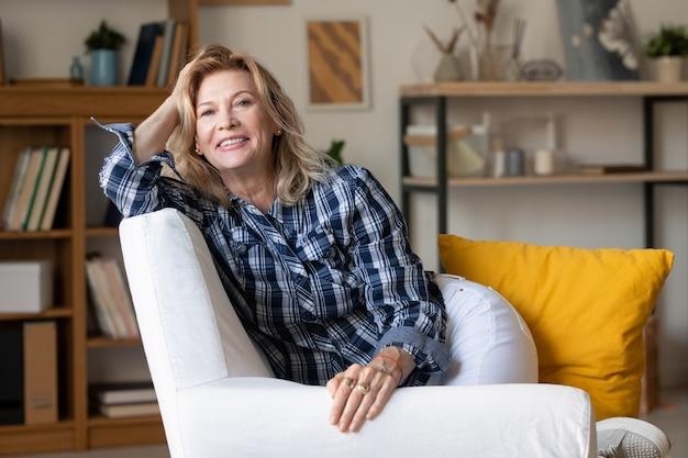 Rijpe blonde vrouw met brede glimlachzitting in comfortabele witte leerleunstoel