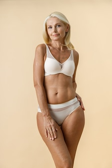 Rijpe blonde vrouw met fit lichaam in wit ondergoed camera kijken terwijl poseren geïsoleerd over