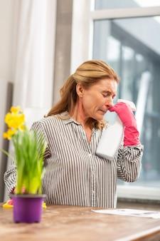 Rijpe blonde vrouw niest en heeft een lopende neus met een sterke allergie