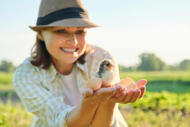 Rijpe boer met pasgeboren kuiken in haar hand