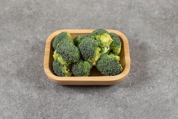 Rijpe broccoli op een bord, op de marmeren tafel.