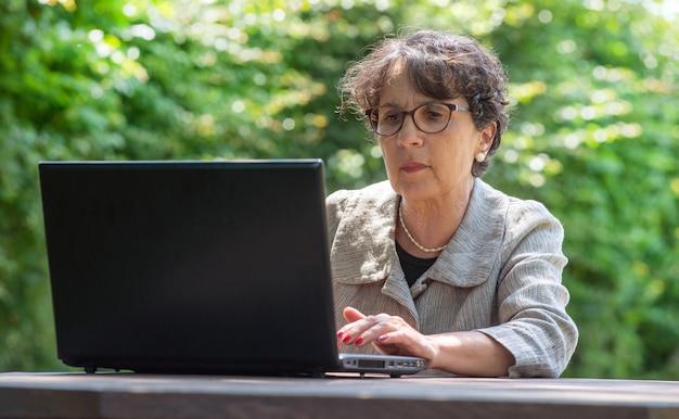 Rijpe brunette die laptop in de tuin met behulp van