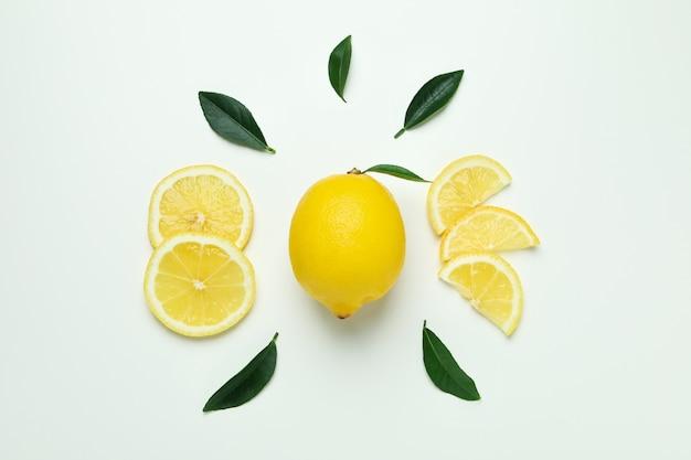 Rijpe citroen en bladeren op wit, bovenaanzicht