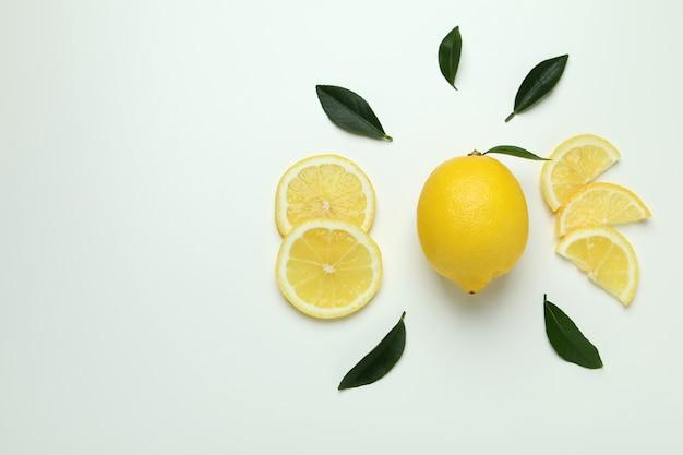 Rijpe citroen en bladeren op wit